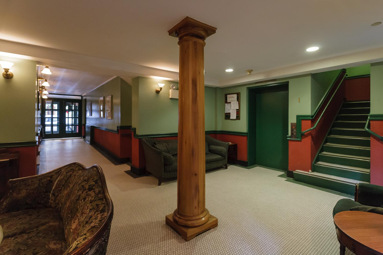 The elevator lobby with restored antique furnishings doubles as a resident lounge at Nero Wolfe.