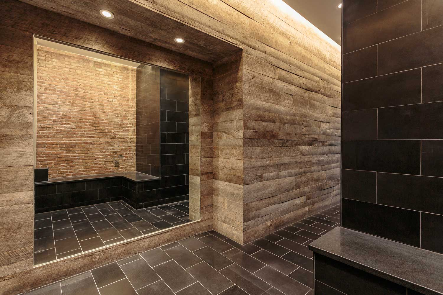 OCV Architects' renovation pairs granite with brick and reclaimed wood wall panels.