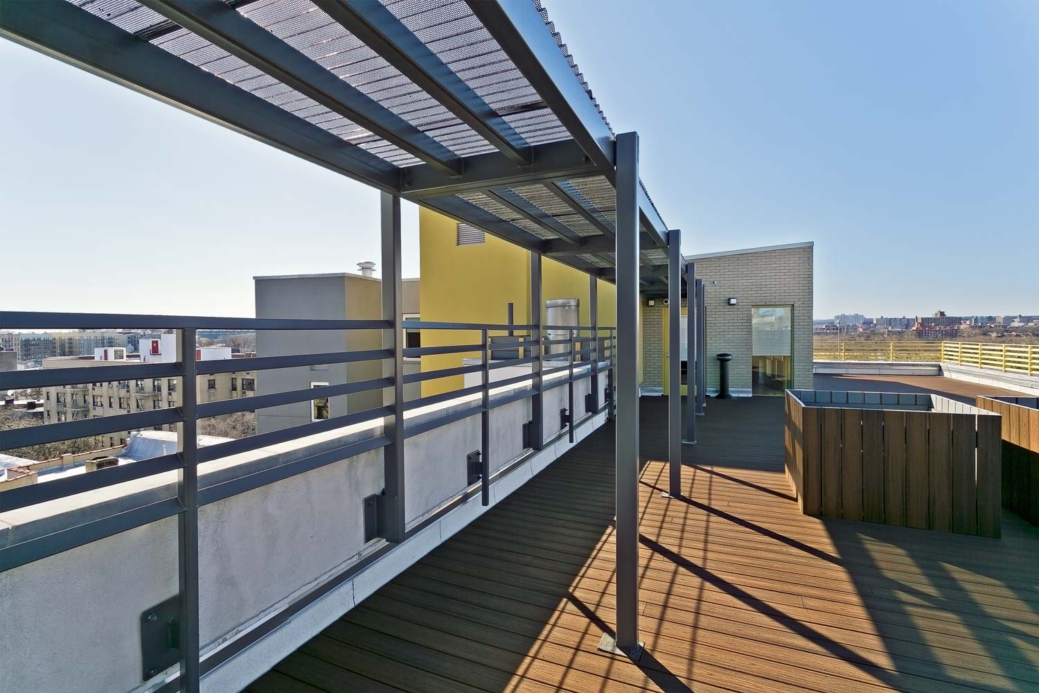 A large community room at the roof level is connected to a paved rooftop terrace.