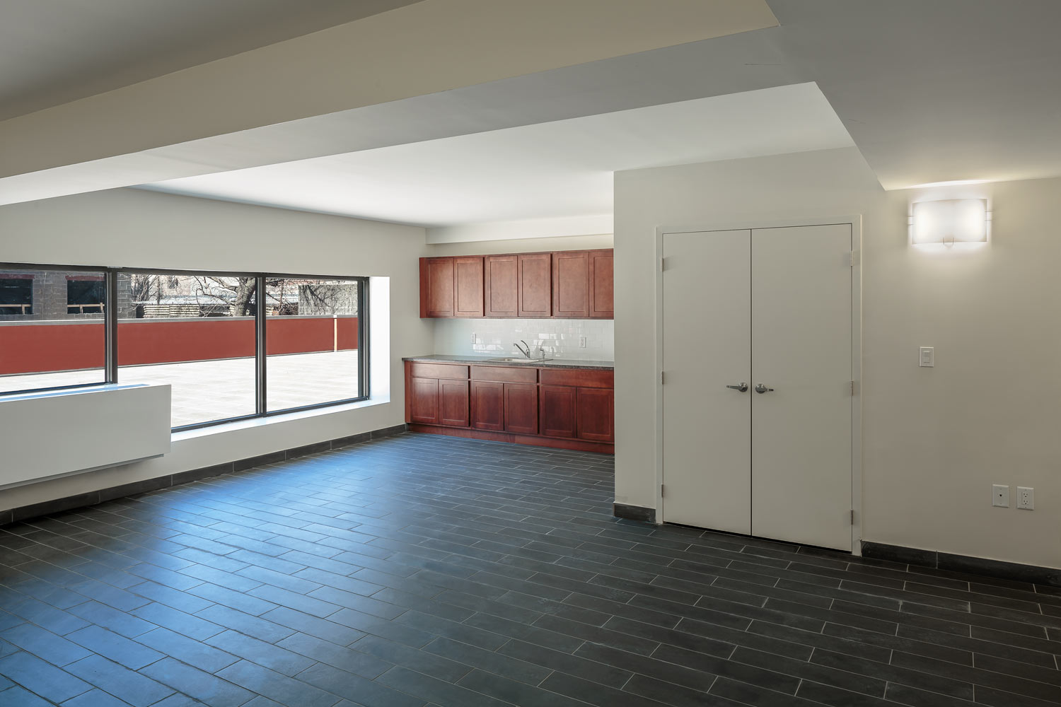 The second floor community room with rear terrace for resident use.