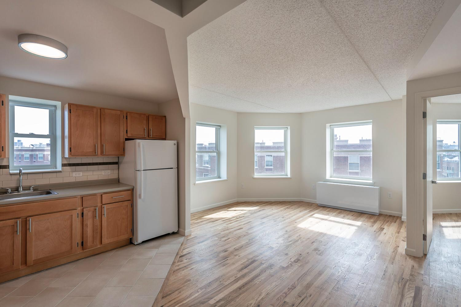 One-bedroom units with bay windows and open living-kitchens in the new construction.