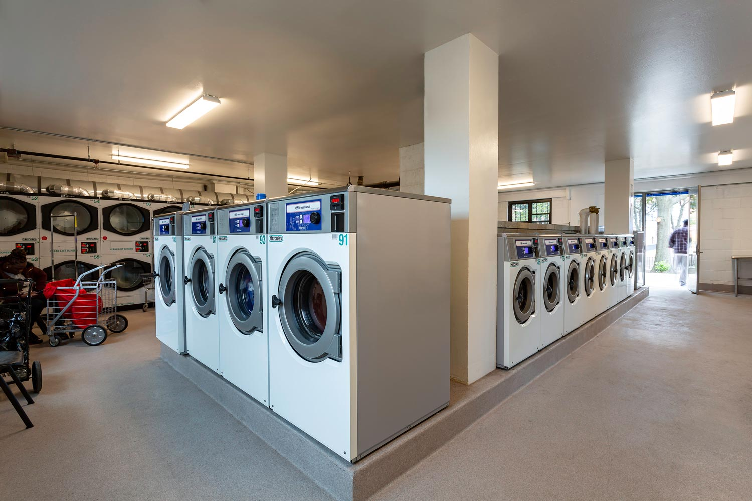 New high efficiency washing machines and dryers in laundry rooms.