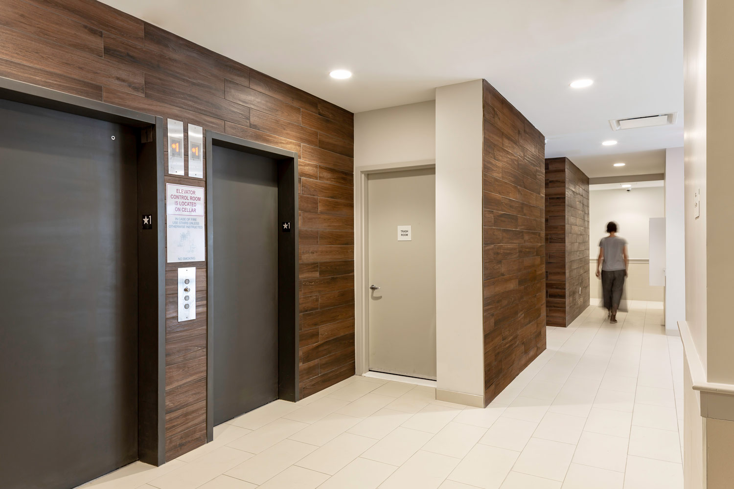 Elevator lobby walls are clad in a wood finish to bring warmth to the space.